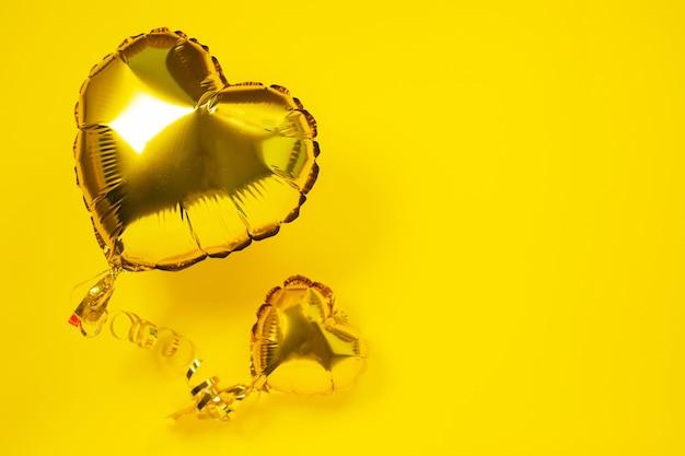 Żółte balony foliowe w kształcie serca na żółtym tle