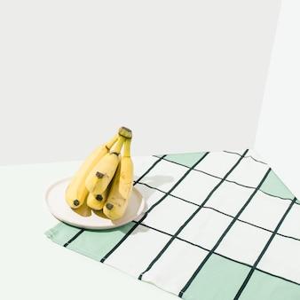 Żółte banany na kuchennym stole i obrusie w paski. pastelowe tło. skandynawskie wnętrze.