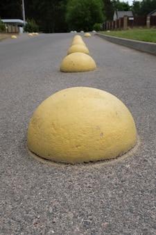 Żółte betonowe półkule na parkingu przy supermarkecie, aby samochody nie parkowały w tym miejscu. sztuczna przeszkoda do jazdy i parkowania. bariera antyparkingowa. zdjęcie wysokiej jakości