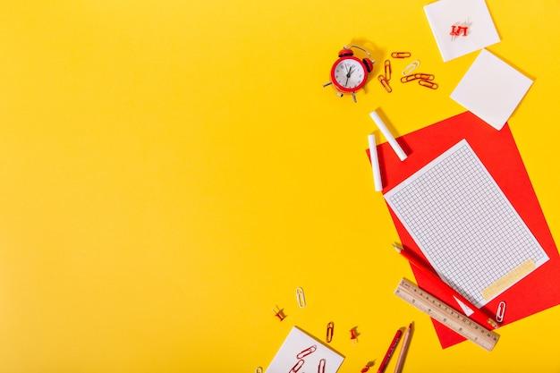 Żółte biurko szkolne jest pełne pięknych papeterii leżących w kreatywny sposób.
