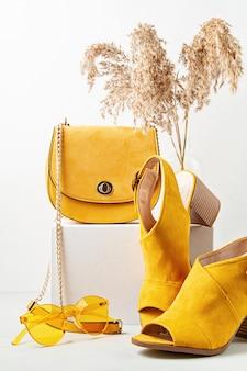 Żółte buty, okulary przeciwsłoneczne i torebka