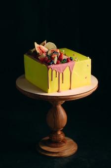 Żółte ciasto cytrusowe ozdobione figami, malinami, jagodami i cytryną.