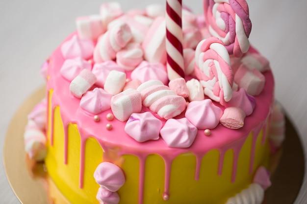 Żółte ciasto dla dzieci z różowym lukrem, bezą i cukierkami