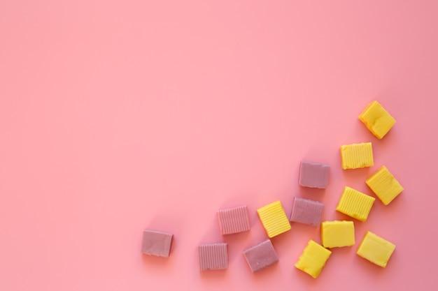 Żółte cukierki do żucia na różowym tle.