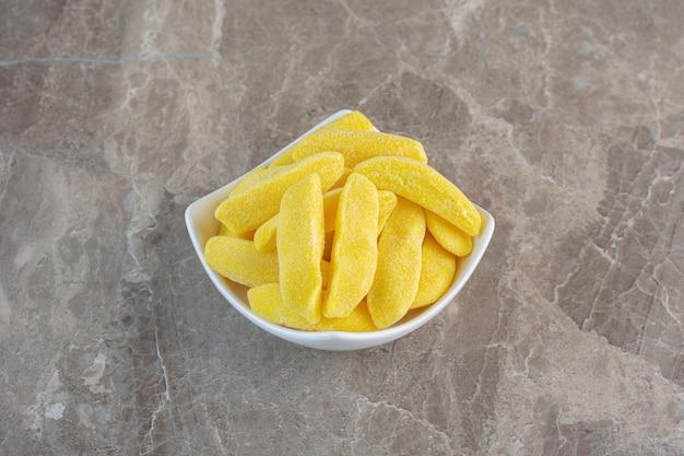 Żółte cukierki do żucia owocowe w białej misce na szarej powierzchni.