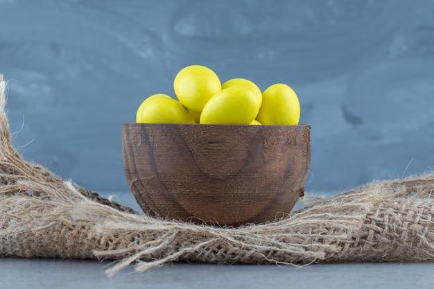 Żółte cukierki w filiżance na podstawce, na marmurowym stole.