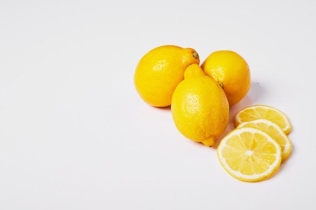 Żółte cytryny na białym tle.
