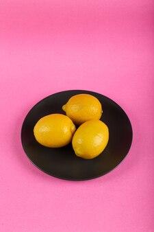 Żółte cytryny na czarnym talerzu na menchiach
