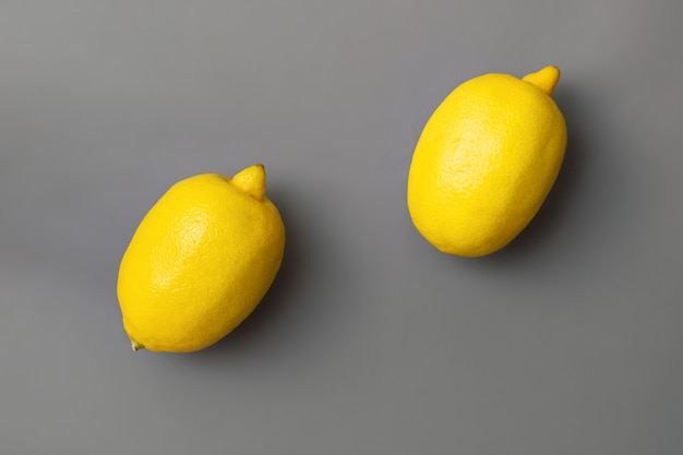 Żółte cytryny na szarym tle. kolory roku 2021 pantone illuminating i ultimate grey. leżał na płasko. skopiuj miejsce