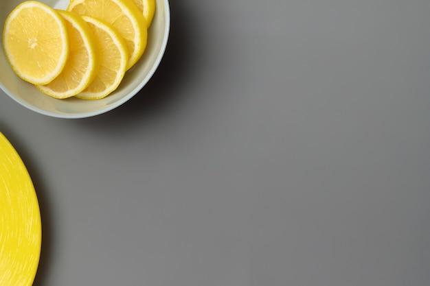 Żółte cytryny w szarym talerzu na szarym tle