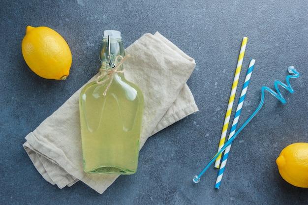 Żółte cytryny z sokiem z cytryny na białej tkaninie i słomkach leżały płasko na białej powierzchni
