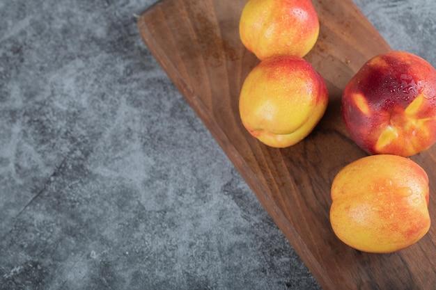 Żółte czerwone brzoskwinie na drewnianym talerzu.