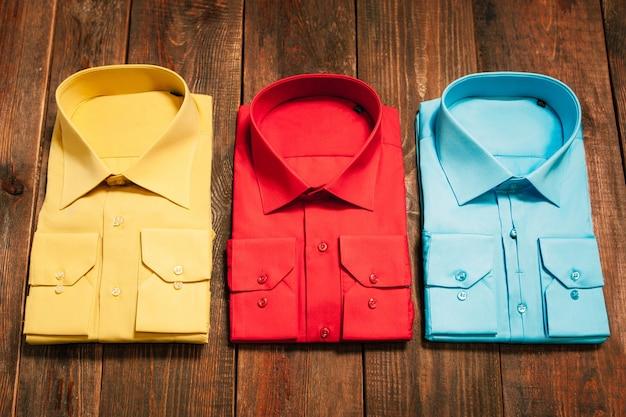 Żółte czerwone niebieskie męskie koszule drewniany stół