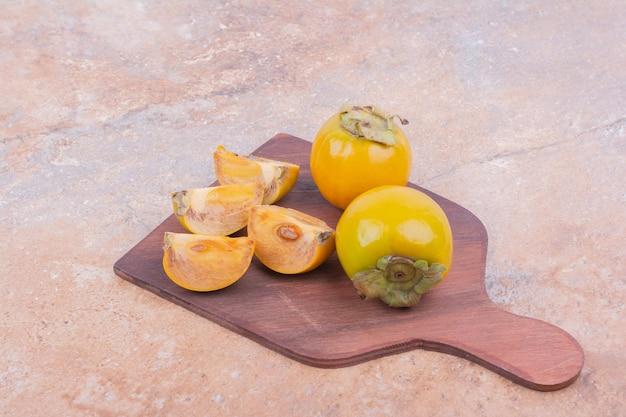 Żółte daktyle śliwkowe na białym tle na drewnianym talerzu.