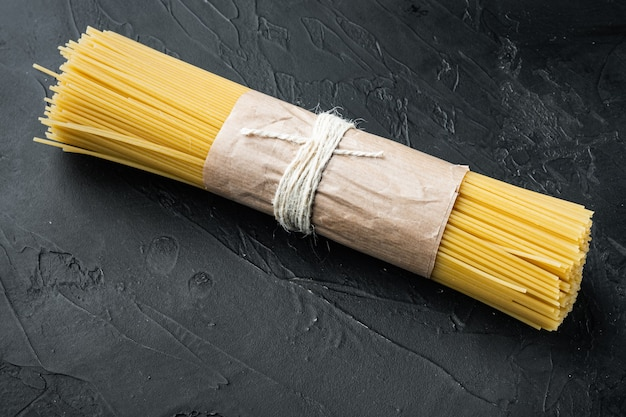 Żółte długie spaghetti, żółty włoski makaron na czarnym tle