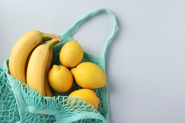 Żółte dojrzałe banany i cytryny w turkusowej siatkowej torbie na lekkiej powierzchni, koncepcja zero waste, miejsce na tekst
