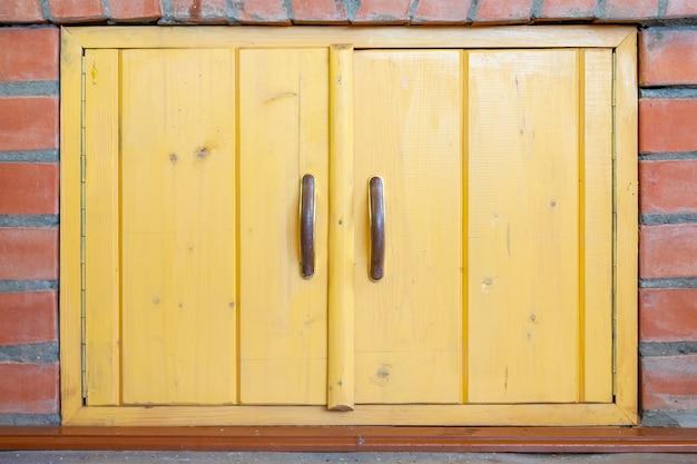 Żółte drewniane drzwi szafy z brązowymi uchwytami