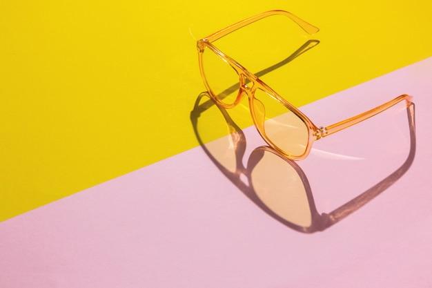 Żółte duże przezroczyste okulary na streszczenie różowy ukośne tło z miejsca na tekst