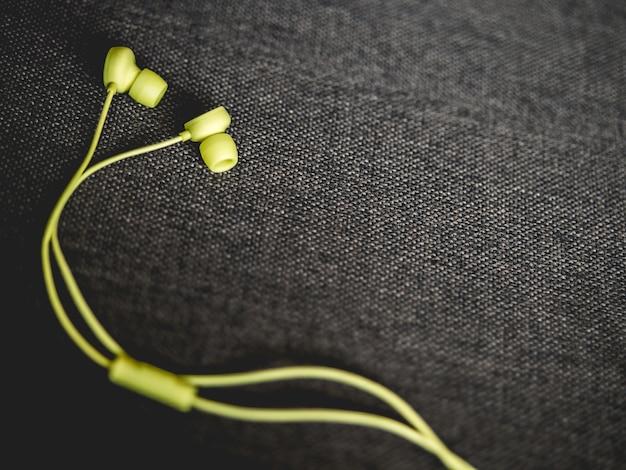 Żółte earbuds na ciemnobrązowej kanapy tle.