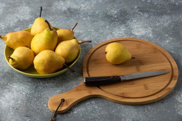Żółte gruszki w bulionie na betonowym stole z drewnianą deską na bok.