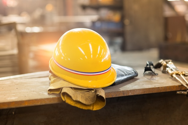 Żółte hardhat i stare skórzane rękawiczki