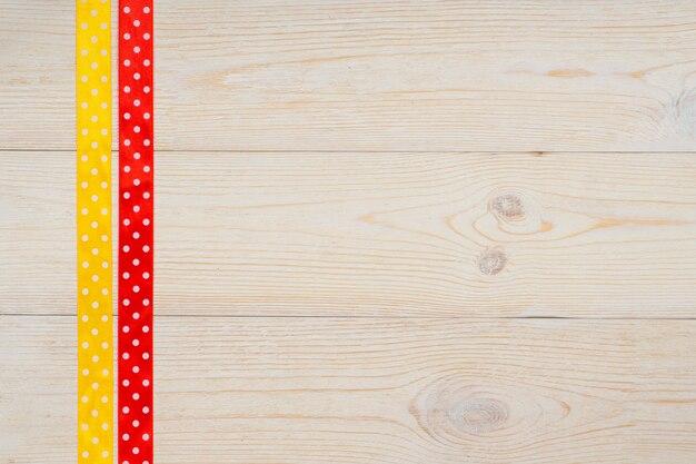 Żółte i czerwone kropki wstążki na drewnianym stole