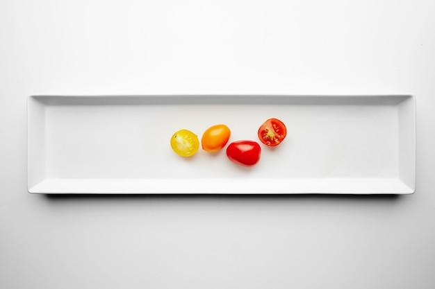 Żółte i czerwone pomidory czereśniowe na białym talerzu z podzieloną połowę, widok z góry