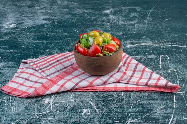 Żółte i czerwone pomidory czereśniowe na białym tle na niebieskiej powierzchni.