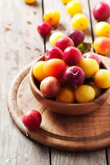 Żółte i czerwone słodkie śliwki na drewnianym stole