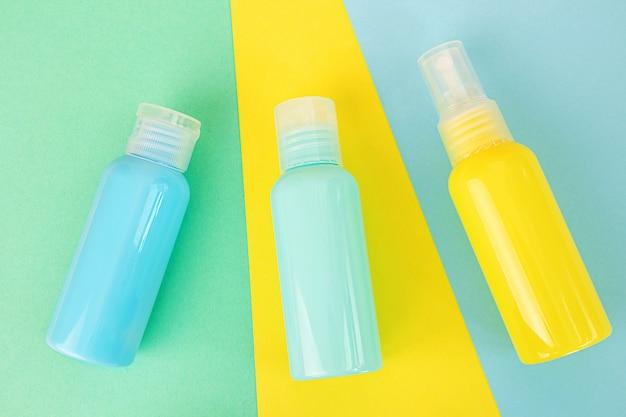 Żółte i niebieskie butelki kosmetyczne na tej samej kolorowej przestrzeni. stylowa koncepcja esencji organicznych, produktów kosmetycznych i zdrowotnych. kopiowanie przestrzeni, minimalizm, płaski układ.