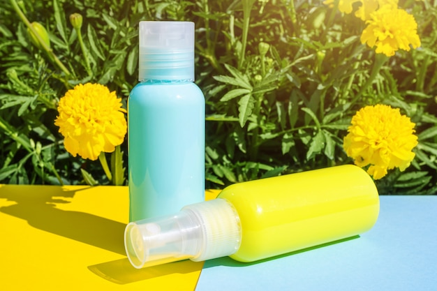 Żółte i niebieskie butelki kosmetyczne na tych samych kolorowych polach. żółte kwiaty są w tyle. stylowa koncepcja esencji organicznych, naturalnych produktów kosmetycznych i zdrowotnych.