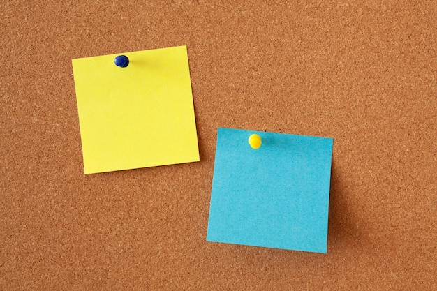 Żółte i niebieskie kartki na notatki na tablicy korkowej. powierzchnia biurowa lub biznesowa.
