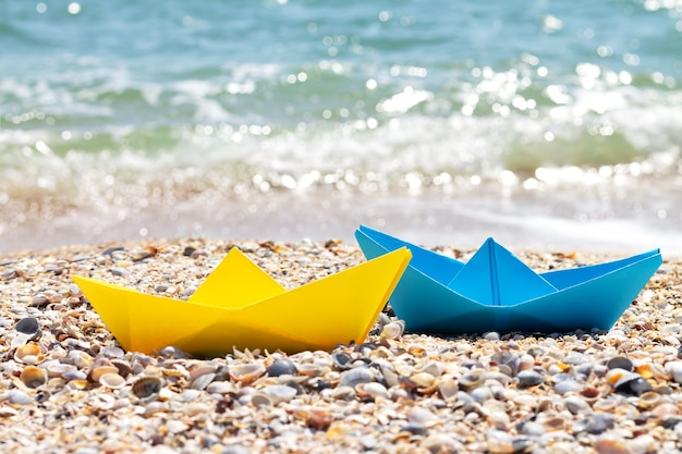 Żółte i niebieskie papierowe łodzie origami na plaży