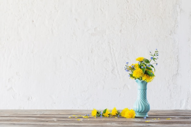 Żółte i niebieskie wiosenne kwiaty s w niebieskim wazonie na białym tle