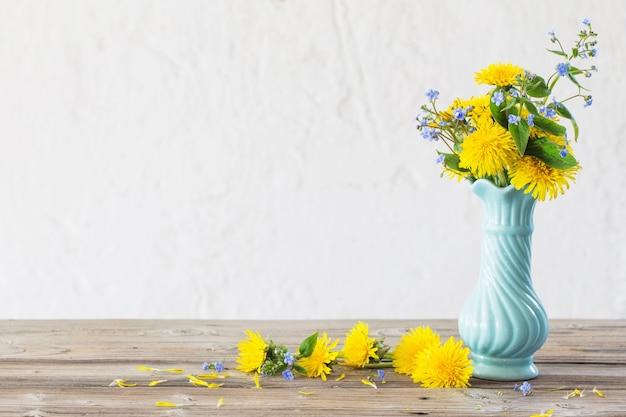 Żółte i niebieskie wiosenne kwiaty w niebieskim wazonie na białym tle