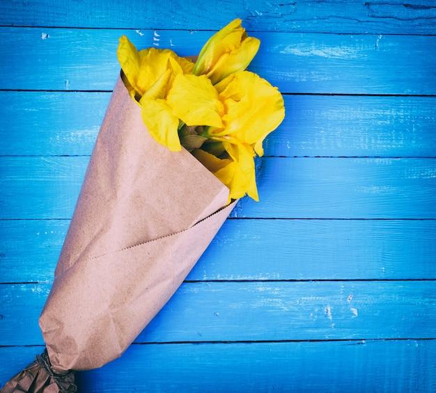 Żółte irysy owinięte w brązowy papier pakowy