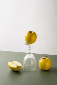Żółte jabłko na szklanej stopce