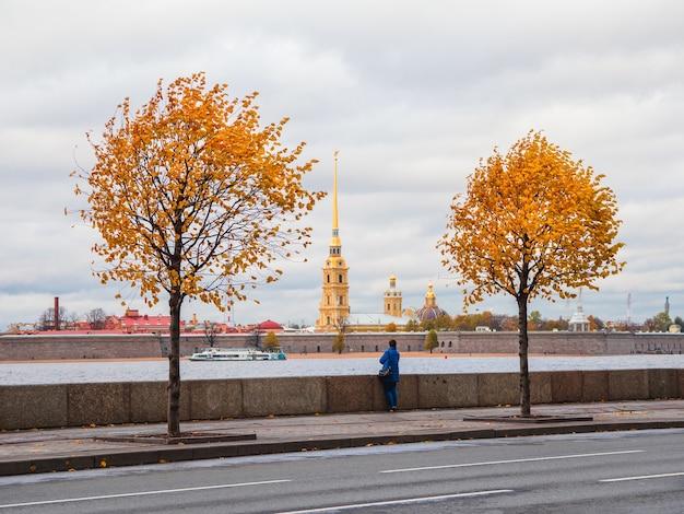 Żółte jesienne drzewa na granitowym nasypie w sankt petersburgu z ludźmi spacerującymi jesienią.