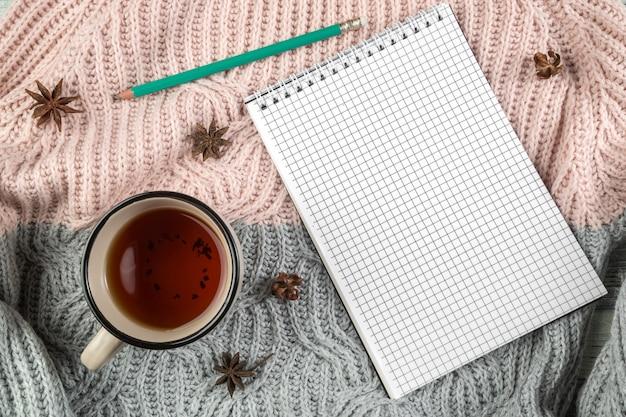 Żółte jesienne liście, filiżanka herbaty i notatnik na teksturowanym swetrze