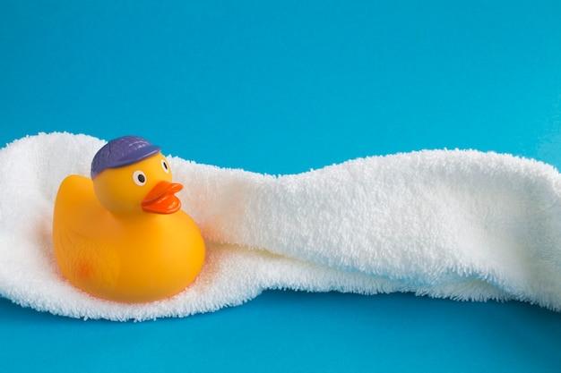 Żółte kaczątko do kąpieli i biały ręcznik na niebieskim tle. skopiuj miejsce. zbliżenie.