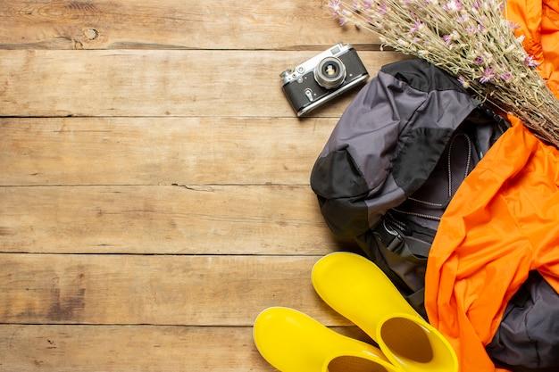 Żółte kalosze, plecak, lornetka, kurtka, sprzęt kempingowy na drewnianym tle. koncepcja turystyki pieszej, turystyki, obozu, gór, lasu.