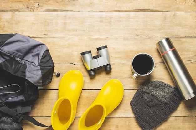 Żółte kalosze, plecak, lornetki, sprzęt kempingowy na drewnianym tle. koncepcja turystyki pieszej, turystyki, obozu, gór, lasu.