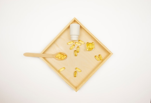 Żółte kapsułki omega 3 leżą na drewnianej tacy
