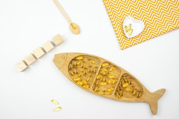 Żółte kapsułki omega 3 leżą na drewnianym talerzu w postaci ryby