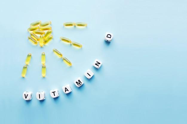 Żółte kapsułki w postaci słońca z promieniami i słowo witamina d