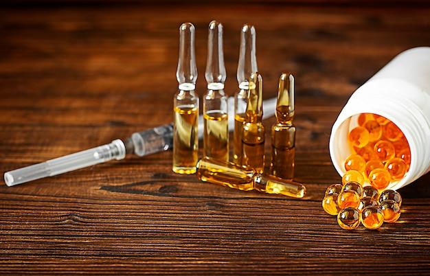 Żółte kapsułki żelowe witaminy d3 są rozproszone z bańki na drewnianym tlew tle otwarty biały słoik z kapsułkami wypełnionymi kapsułkami kilka szklanych ampułek do wstrzykiwań strzykawka