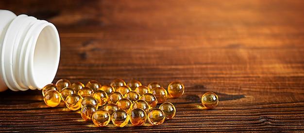 Żółte kapsułki żelowe witaminy d3 są rozproszone z bańki na drewnianym tlew tle otwarty biały słoik z kapsułkami wypełnionymi kapsułkami skopiuj miejsce