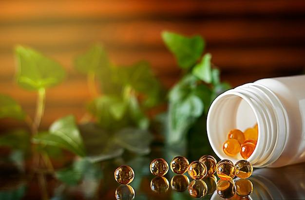 Żółte kapsułki żelowe witaminy d3 są rozproszone z bańki odbite na szklanej powierzchni w tle jest otwarty biały słoik z kapsułkami wypełnionymi kapsułkami kopiowanie miejsca drewniane tło an