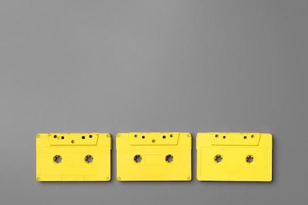 Żółte kasety audio na szarym tle widok z góry, kopia przestrzeń