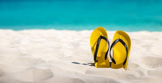 Żółte klapki na piaszczystej plaży.